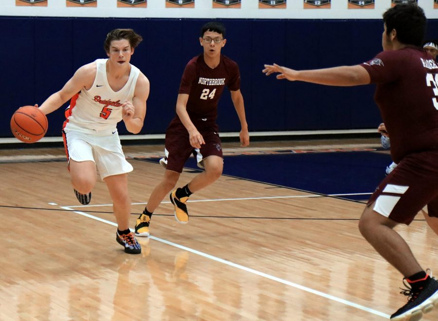 Junior Nate Weeks drives past Northbrook defenders.