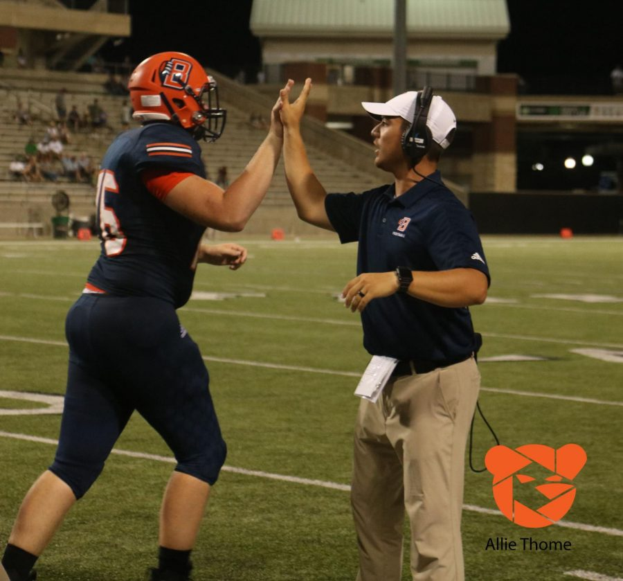 Coach Rader gives a high five of encouragement. Photo by Allie Thome