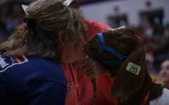Two staff members kiss goat for FFA fundraiser