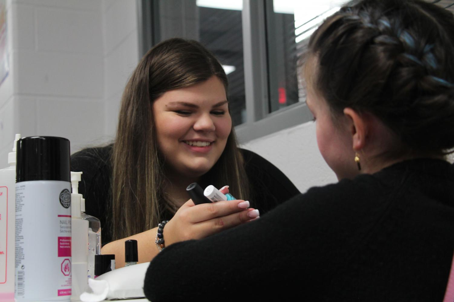 Lois Hill works on her nail art in class.