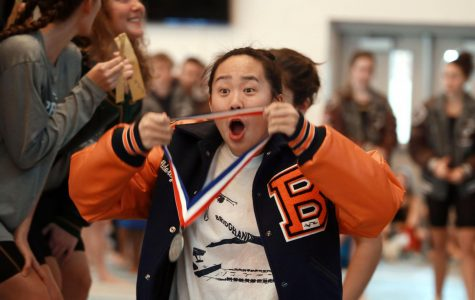 Junior Aldercy Bui shows her second place medal to her team.