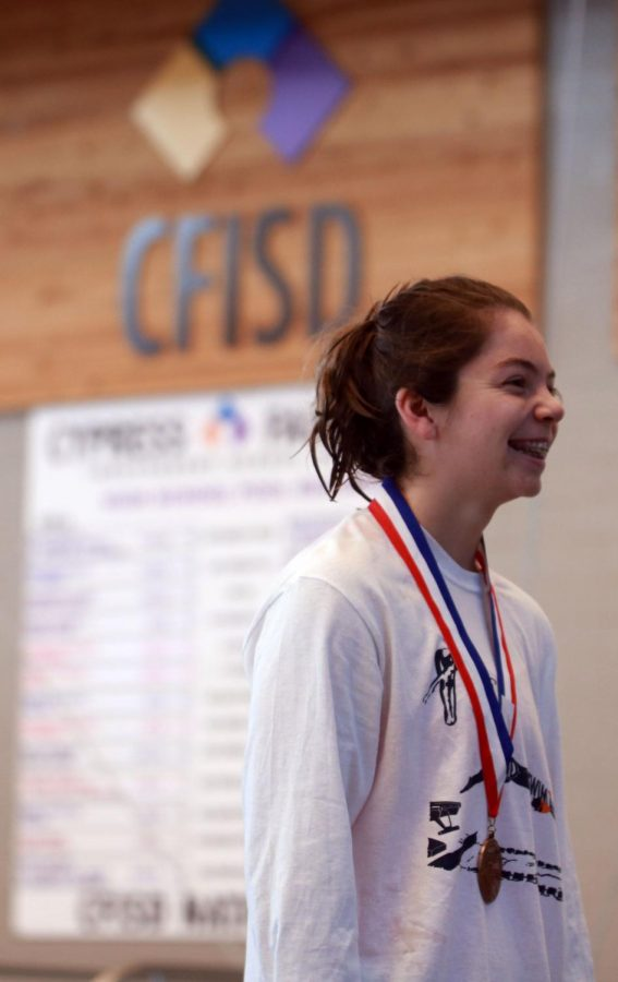 Freshman Emma Kinsey stands on the podium of her first varsity districts. Kinsey placed tenth at the state meet with a time of 56.39 in the 100 Fly.