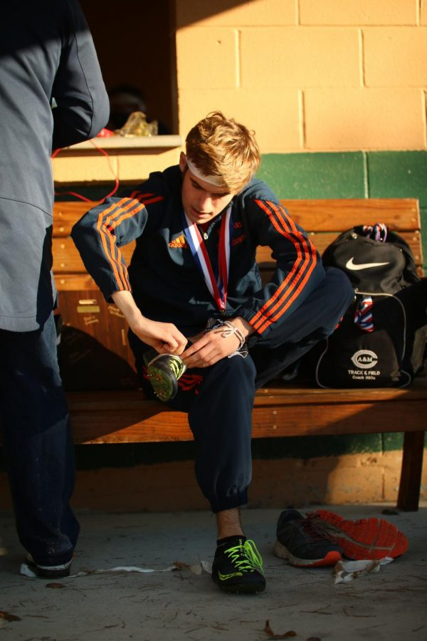 SPORTS - OTHER PHOTO OF THE MONTH: Taking off his spikes after placing second in the district cross country meet, senior Jacob Grosch prepares to begin his warm-down.