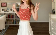 Bella smiles for the camera in a cropped patterned cami and a pleated white tennis skirt.