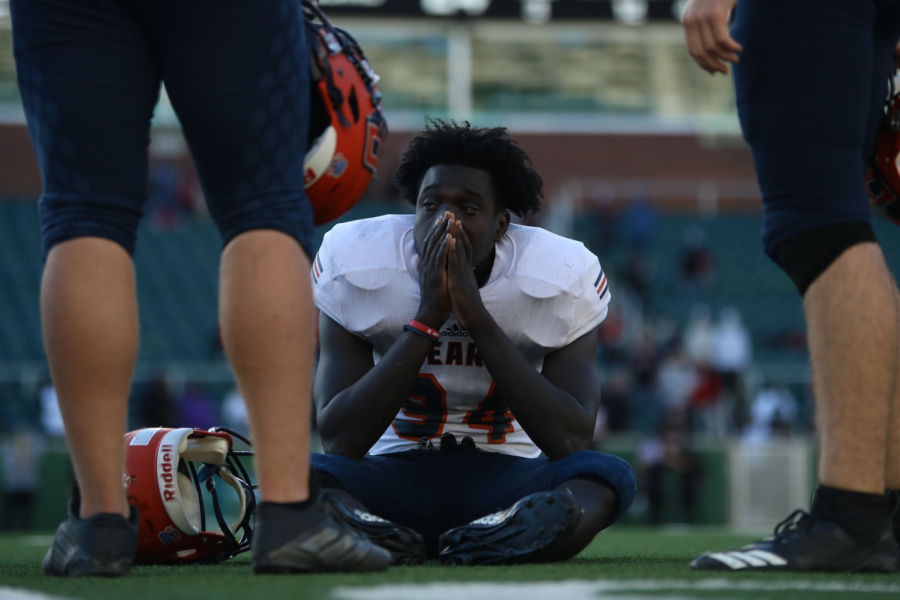 Senior defensive lineman Aundre' Dewalt sits with tears in his eyes after the game against Rockwell-Heath.