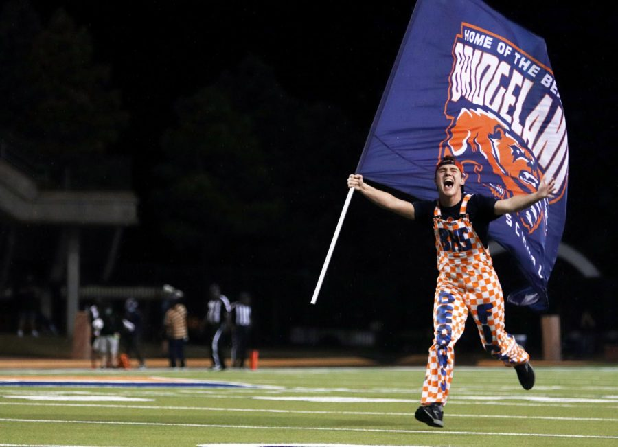 After a touchdown, Claw Crew member junior Cade Sanders runs across the field flag in hand.