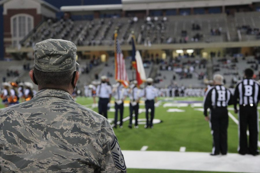 Captain Michael Claiborn stands on the sidelines as ROTC cadets present the flags during the National Anthem at the varsity football game against Cy Park.